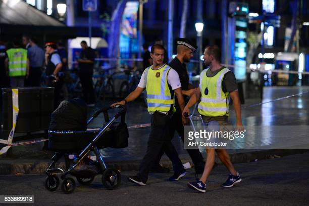 Spanish policemen accompany a baby in his pram outside the cordoned off area after a van ploughed into the crowd killing 13 persons and injuring over...