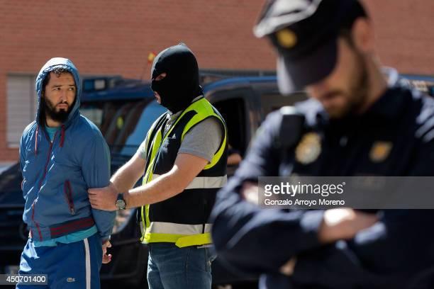 Spanish policemen arrest a man suspected of belonging to an international Jihadist recruiting network at Rutilo street on June 16 2014 in Madrid...