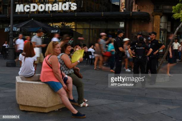 Spanish policemen chat as people sit on concrete barriers displayed at the entrance of a pedestrian street near Gran Via in Madrid on August 19 two...