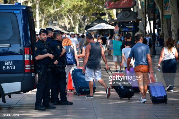 Spanish policemen stand guard as tourists pass by with their suitcases on the Rambla boulevard on August 18 2017 a day after a van ploughed into the...
