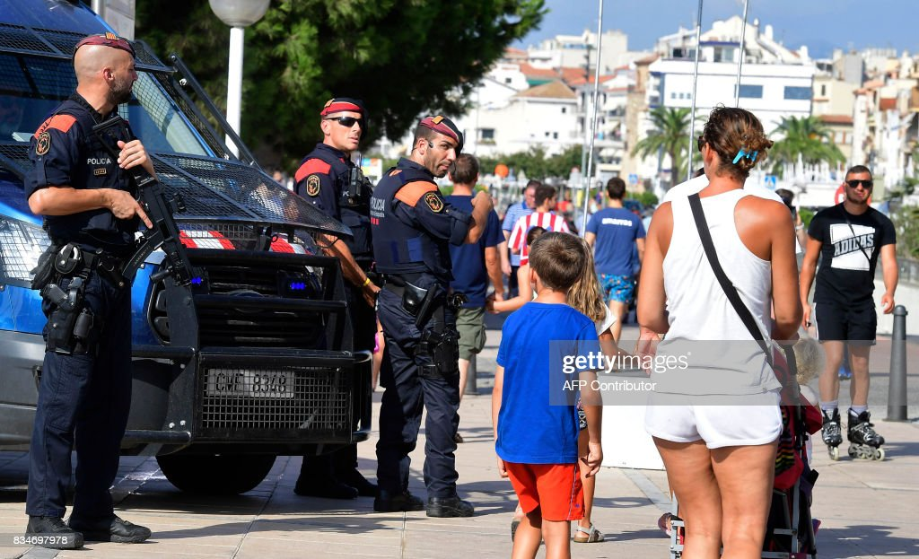 Spanish policemen stand guard in Cambrils on August 18, 2017, a day after a van ploughed into the crowd, killing 13 persons and injuring over 100 on the Rambla in Barcelona. Drivers have ploughed on August 17, 2017 into pedestrians in two quick-succession, separate attacks in Barcelona and another popular Spanish seaside city, leaving 13 people dead and injuring more than 100 others. In the first incident, which was claimed by the Islamic State group, a white van sped into a street packed full of tourists in central Barcelona on Thursday afternoon, knocking people out of the way and killing 13 in a scene of chaos and horror. Some eight hours later in Cambrils, a city 120 kilometres south of Barcelona, an Audi A3 car rammed into pedestrians, injuring six civilians -- one of them critical -- and a police officer, authorities said. /