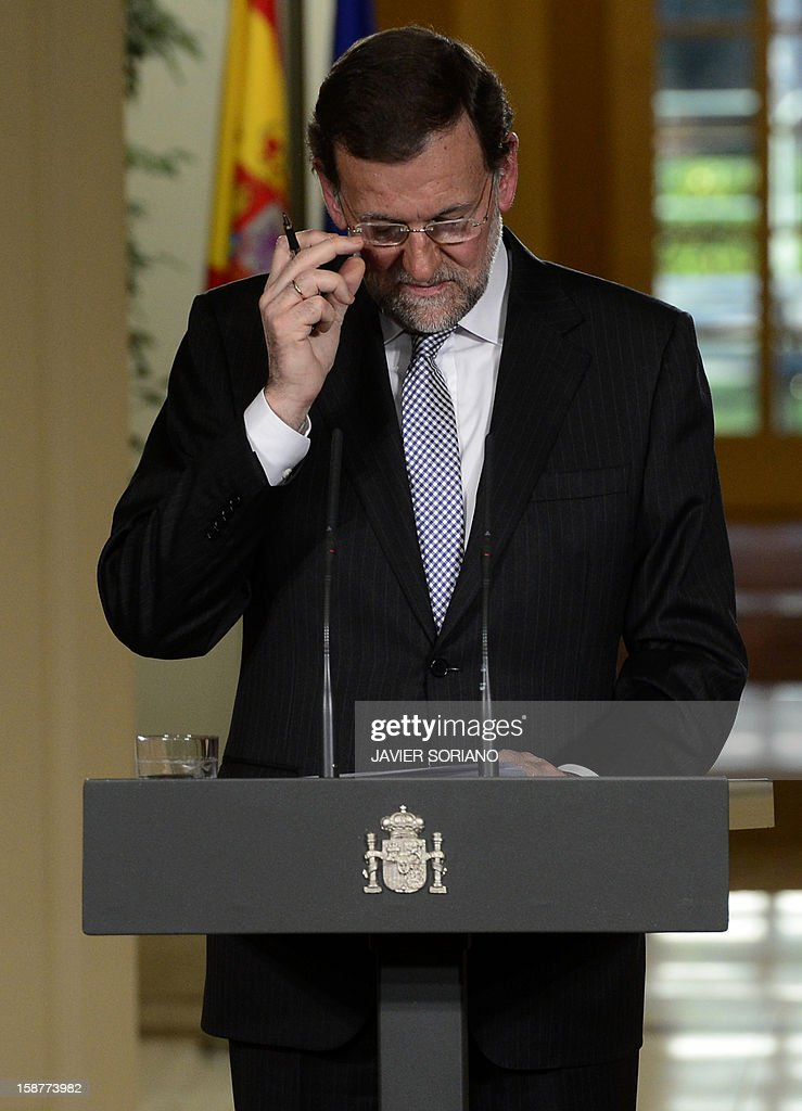 Spanish Prime Minister and PP (Popular Party) leader Mariano Rajoy adjusts his glasses as he speaks during a press conference at the Moncloa Palace in Madrid on December 28, 2012. Rajoy warned today of a 'very tough' year ahead for the recession-struck economy but said he hoped for an improvement in the second half of 2013. AFP PHOTO/ JAVIER SORIANO