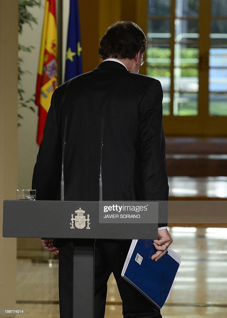 Spanish Prime Minister and PP (Popular Party) leader Mariano Rajoy leaves at the end of a press conference at the Moncloa Palace in Madrid on December 28, 2012. Rajoy warned today of a 'very tough' year ahead for the recession-struck economy but said he hoped for an improvement in the second half of 2013. AFP PHOTO/ JAVIER SORIANO