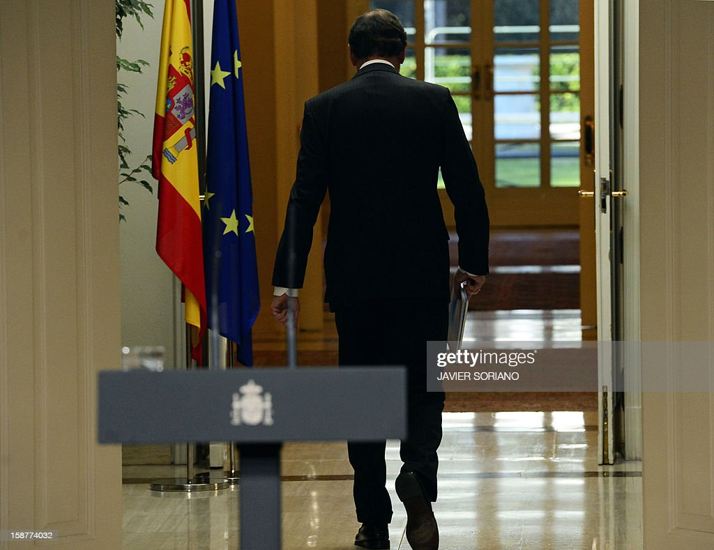 Spanish Prime Minister and PP (Popular Party) leader Mariano Rajoy leaves at the end of a press conference at the Moncloa Palace in Madrid on December 28, 2012. Rajoy warned today of a 'very tough' year ahead for the recession-struck economy but said he hoped for an improvement in the second half of 2013.