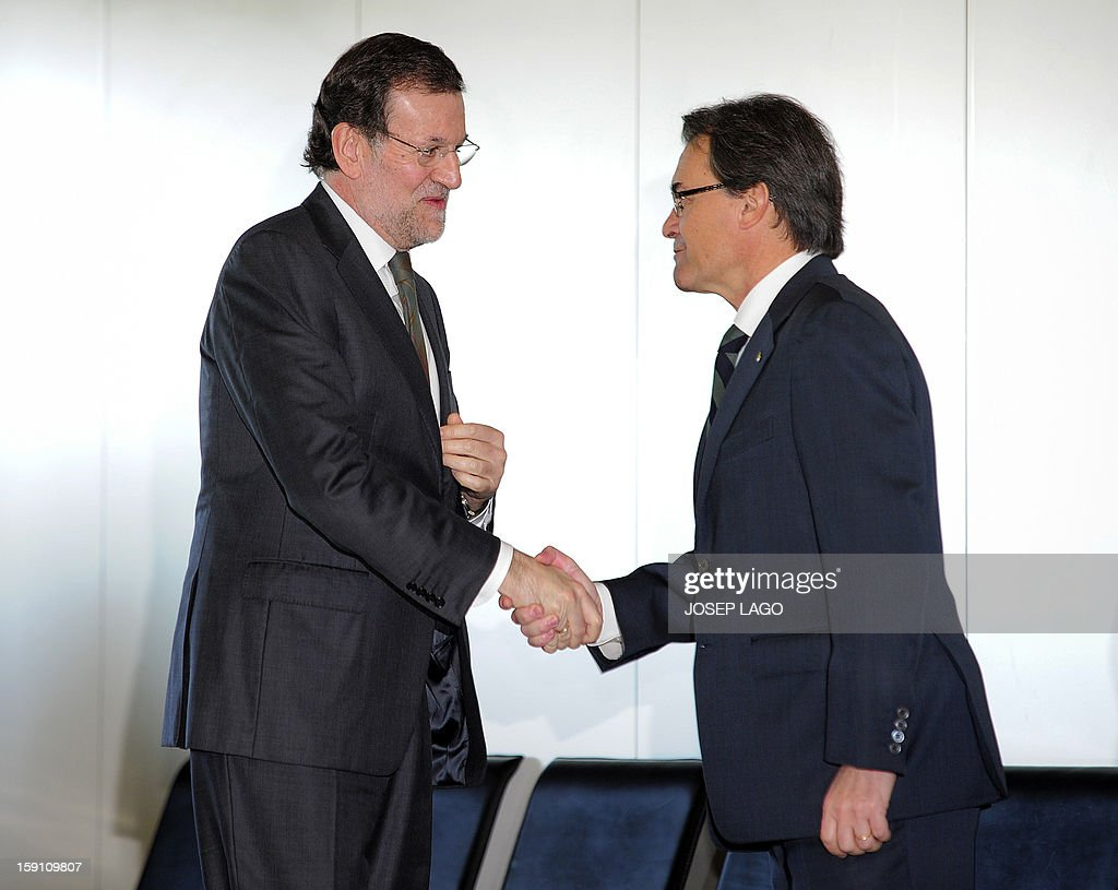 Spanish Prime Minister and PP (Popular Party) leader Mariano Rajoy (L) shakes hands with President of the Catalonia regional government and leader of the Catalan party CIU (Convergence and Unity party) Artur Mas prior to onboard a train at Sants, the Barcelona's train station, during the inauguration of the high-speed line between Barcelona and the french border, on January 8, 2013. AFP PHOTO/ JOSEP LAGO