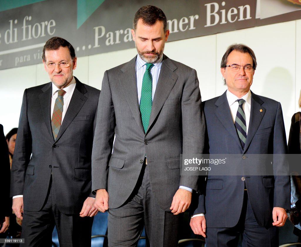 Spanish Prime Minister and PP (Popular Party) leader Mariano Rajoy, Spain's Prince Felipe and president of the Catalonia regional government and leader of the Catalan party CIU (Convergence and Unity party) Artur Mas walk get onboard a train at Sants, Barcelona's train station, during the inauguration of the high-speed line between Barcelona and the french border, on January 8, 2013.