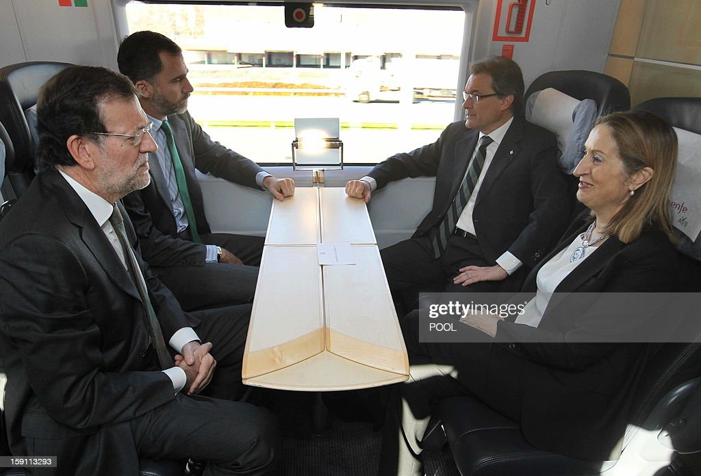 Spanish Prime Minister and PP (Popular Party) leader Mariano Rajoy, Spain's Prince Felipe, President of the Catalonia regional government and leader of the Catalan party CIU (Convergence and Unity party) Artur Mas and Spain's Minister of Development Ana Pastor chat onboard the high-speed train during the inauguration of the high-speed line between Barcelona and the french border, on January 8, 2013.