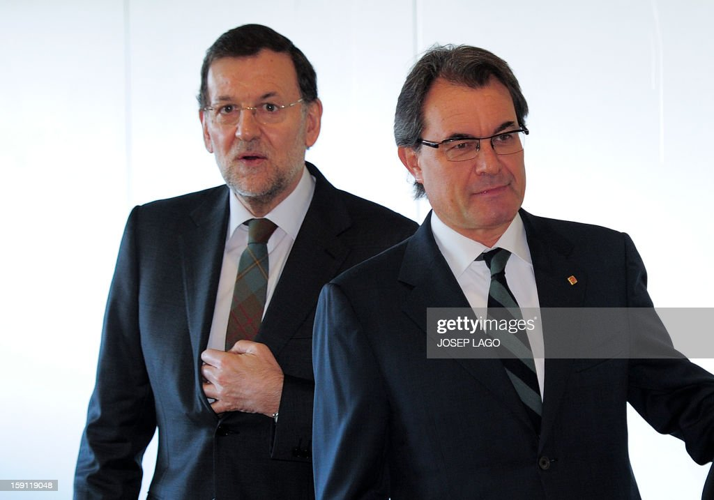 Spanish Prime Minister and PP (Popular Party) leader Mariano Rajoy (L) walks next to president of the Catalonia regional government and leader of the Catalan party CIU (Convergence and Unity party) Artur Mas prior to onboard a train at Sants, Barcelona's train station, during the inauguration of the high-speed line between Barcelona and the french border, on January 8, 2013. AFP PHOTO/ JOSEP LAGO