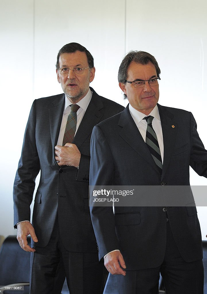 Spanish Prime Minister and PP (Popular Party) leader Mariano Rajoy (L) walks next to president of the Catalonia regional government and leader of the Catalan party CIU (Convergence and Unity party) Artur Mas prior to getting onboard a train at Sants, Barcelona's train station, during the inauguration of the high-speed line between Barcelona and the french border, on January 8, 2013.