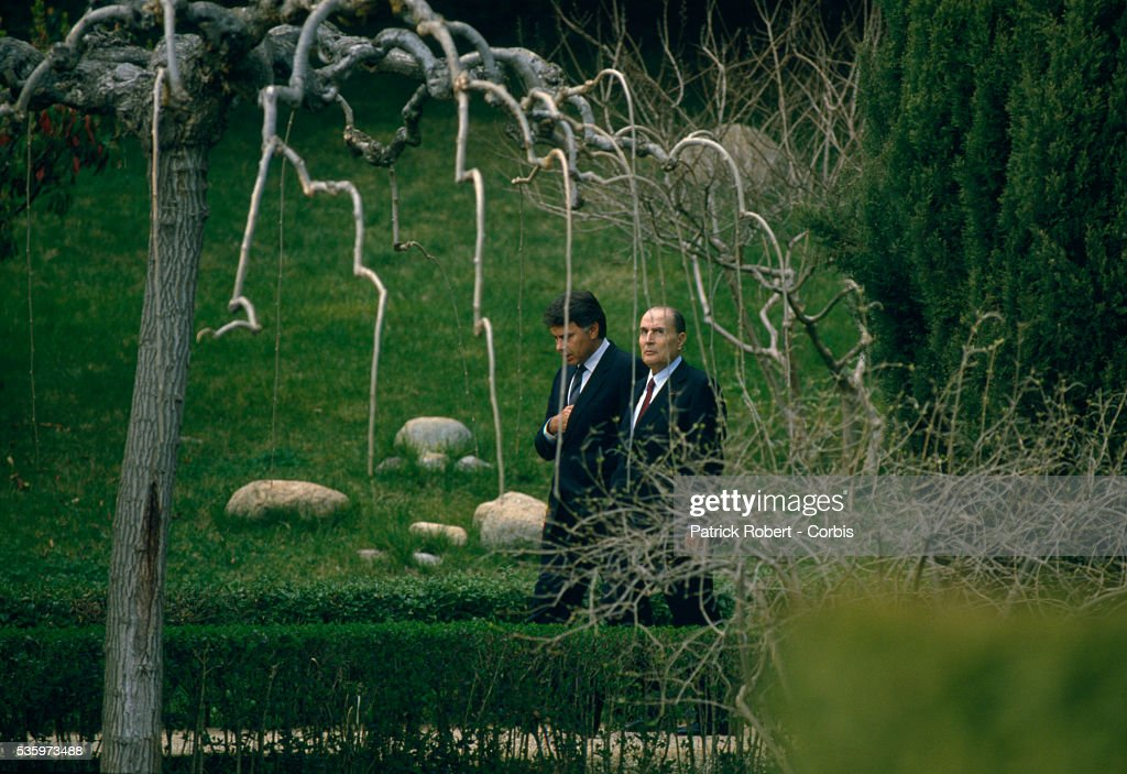 Spanish Prime Minister Felipe Gonzalez (L) and French President Francois Mitterrand converse as they walk through a garden in Madrid. The French and Spanish leaders met in Madrid for the 1987 Franco-Spanish Summit.   Location: Madrid, Spain.