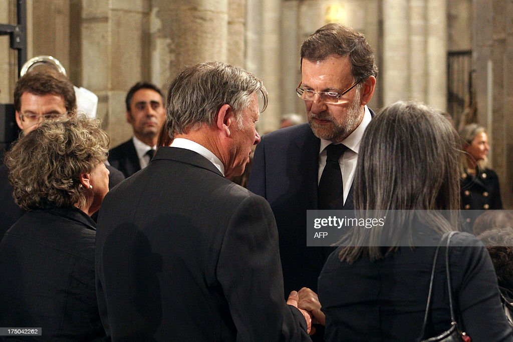 Spanish Prime Minister leader Mariano Rajoy (R) comforts relatives of the victims at the end of a memorial service for the victims the derailed train of Angrois, at the cathedral of Santiago de Compostela on July 29, 2013. The driver of a train that hurtled off the rails in Spain was charged on July 28 with 79 counts of reckless homicide and released on bail after being questioned by a judge.