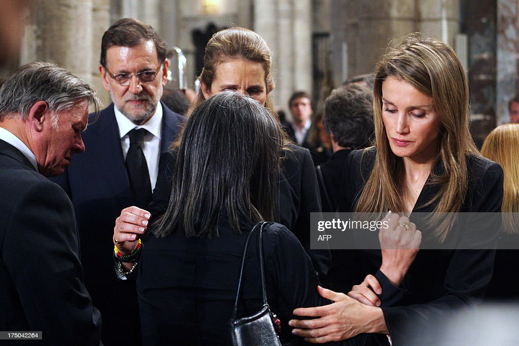 Spanish Prime Minister leader Mariano Rajoy (L), Spain's Infanta Elena (C) and Spain's Princess Letizia (R) comfort relatives of the victims at the end of a memorial service for the victims the derailed train of Angrois, at the cathedral of Santiago de Compostela on July 29, 2013. The driver of a train that hurtled off the rails in Spain was charged on July 28 with 79 counts of reckless homicide and released on bail after being questioned by a judge.