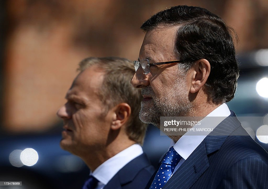 Spanish Prime Minister Mariano Rajoy (R) and his Polish counterpart Donald Tusk listen to national anthems at the Moncloa palace in Madrid on July 15, 2013. AFP PHOTO / PIERRE-PHILIPPE MARCOU