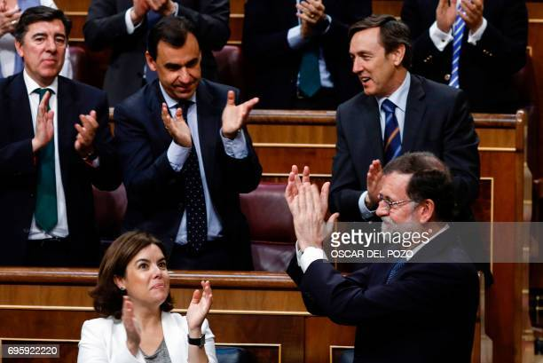 Spanish Prime Minister Mariano Rajoy apllaudes and as he is applauded by his party fellows at the Congress of Deputies in Madrid on June 14 2017...