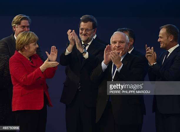 Spanish Prime Minister Mariano Rajoy claps flanked by European People's Party Secretary General Spanish Antonio Lopez Isturiz German Chancellor and...
