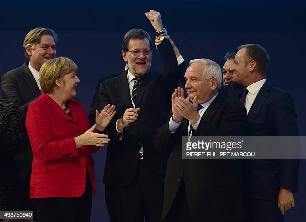 Spanish Prime Minister Mariano Rajoy gestures flanked by European People's Party Secretary General Spanish Antonio Lopez Isturiz German Chancellor...
