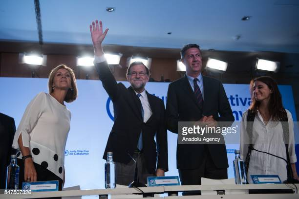 Spanish Prime Minister Mariano Rajoy greets the crowd as he is flanked by leader of the Partido Popular Xavier Garcia Albiol and Spanish Minister of...