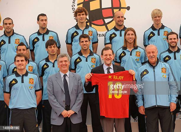 Spanish Prime Minister Mariano Rajoy holds up a Spanish team jersey beside Spanish head coach Vicente del Bosque captain Iker Casillas and the...