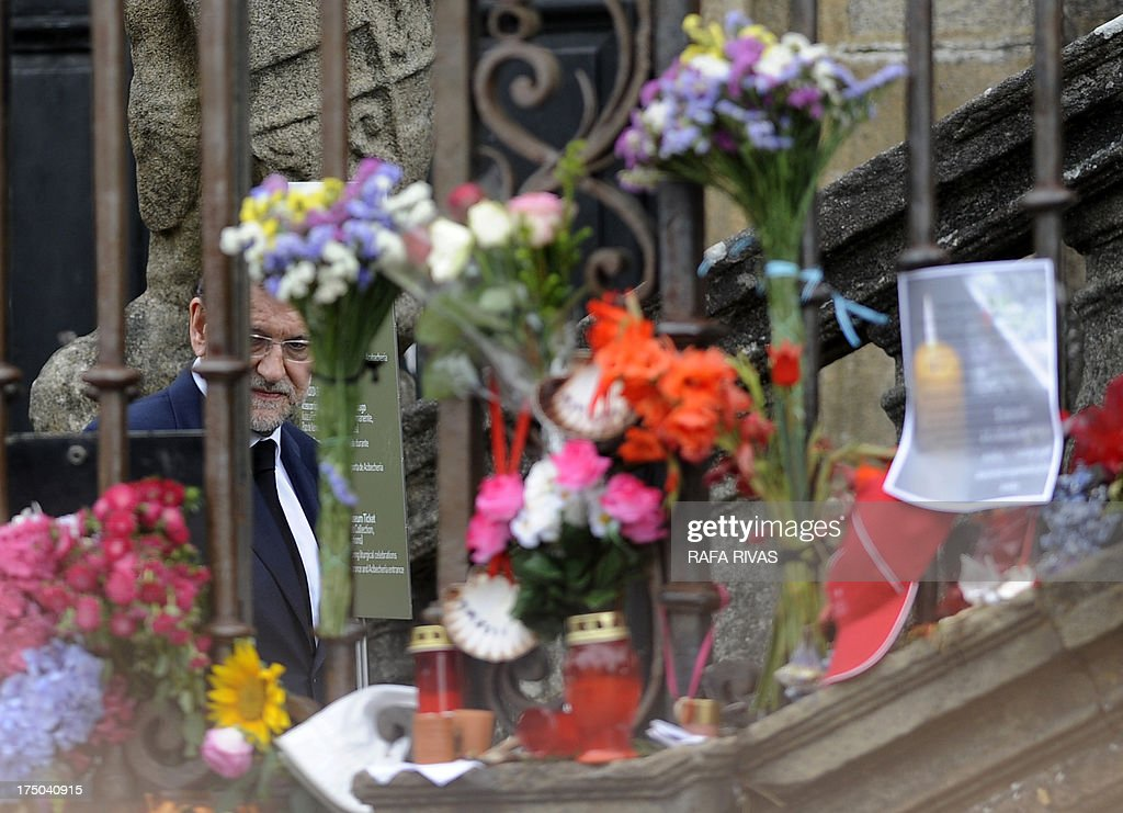 Spanish Prime Minister Mariano Rajoy looks at flowers and candles displayed at the Obradoiro Square as he arrives to attend a memorial service for the victims the derailed train of Angrois, at the cathedral of Santiago de Compostela on July 29, 2013. The driver of a train that hurtled off the rails in Spain was charged on July 28 with 79 counts of reckless homicide and released on bail after being questioned by a judge. AFP PHOTO/ RAFA RIVAS