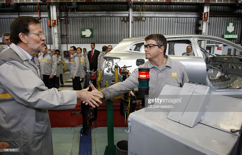 Spanish Prime Minister Mariano Rajoy (L) shakes hands wiht a worker during a visit at the Villamuriel Renault factory in northern Spain on November 21, 2012. French car maker Renault plans to create 1,300 jobs at its factories in recession-hit Spain, Spanish Prime Minister Mariano Rajoy said. Renault has an industrial plan to develop its Spanish plants which will involve 'the creation of 1,300 new jobs', Rajoy said.