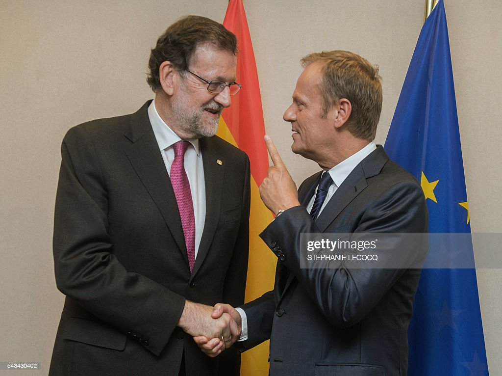 Spanish Prime Minister Mariano Rajoy (L) shakes hands with European Union Council President Donald Tusk ahead of an European Union summit on June 28, 2016 at the EU headquarters in Brussels. Britain's exit from the European Union may erode the bloc's leadership role in fighting climate change and stymie crucial efforts to set more ambitious targets for cutting greenhouse gases, officials and experts said on June 28. European leaders meeting in Brussels pressured British Prime Minister David Cameron Tuesday to launch the two-year withdrawal process 'as soon as possible', but the embattled premier has vowed he will leave that task to a successor to be named on September 9. / AFP / POOL / STEPHANIE