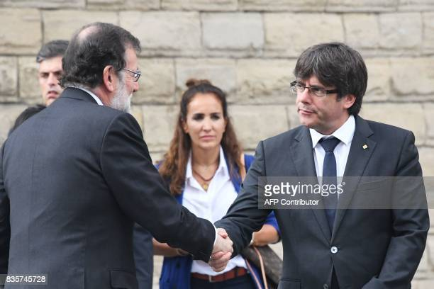 Spanish Prime Minister Mariano Rajoy shakes hands with President of Catalonia Carles Puigdemon upon his arrival for a mass to commemorate victims of...