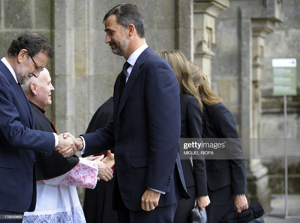 Spanish Prime Minister Mariano Rajoy (L) shakes hands with Spain's Prince Felipe as he arrives to attend a memorial service for the victims the derailed train of Angrois, at the cathedral of Santiago de Compostela on July 29, 2013. The driver of a train that hurtled off the rails in Spain was charged on July 28 with 79 counts of reckless homicide and released on bail after being questioned by a judge. AFP PHOTO/ POOL/ MIGUEL RIOPA