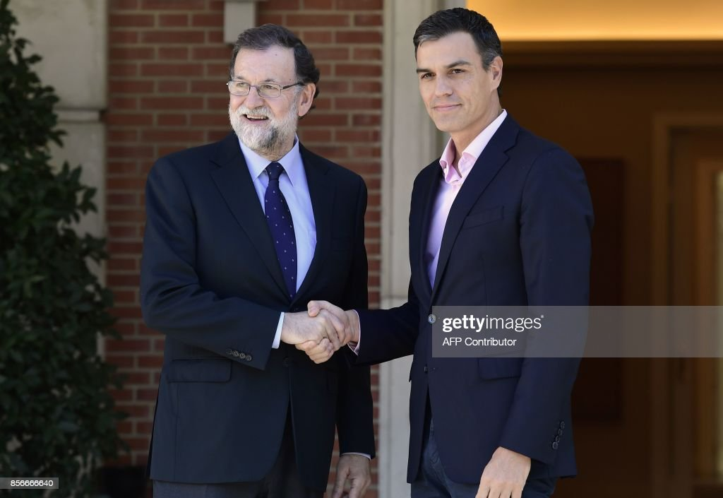 Spanish Prime Minister Mariano Rajoy (L) shakes hands with Spanish Socialist Party PSOE leader Pedro Sanchez prior to holding a meeting at La Moncloa palace in Madrid on October 2, 2017. Spain came under international pressure today to resolve a spiralling crisis with its Catalan region after a banned independence referendum was marred by shocking scenes of police violence. /