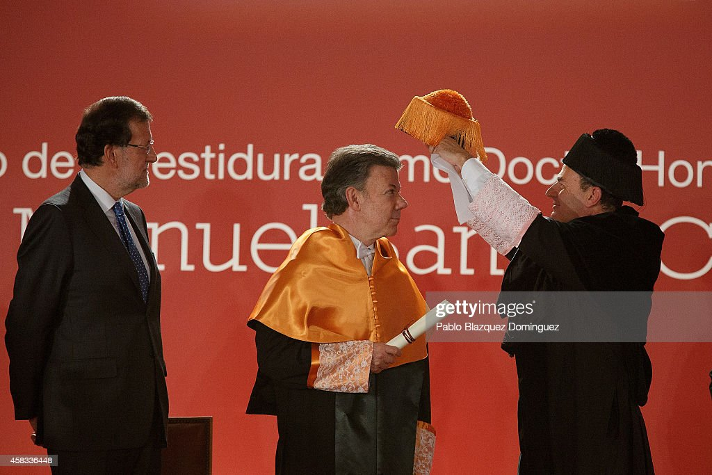 Spanish Prime Minister Mariano Rajoy (L) stands next to Colombia's President Juan Manuel Santos (C) as he receives an Honorary Doctorate during a ceremony at the Camilo Jose Cela university on November 3, 2014 in Villafranca del Castillo, just outside Madrid, Spain. Juan Manuel Santos is on an official visit to Spain which will follow with visits to other European cities.