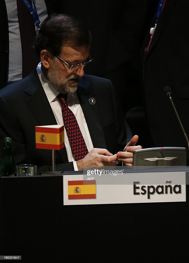 Spanish Prime Minister Mariano Rajoy uses his mobile phone during the closing ceremony of the Latin American and Caribbean States (CELAC)-European Union (EU) Summit in Santiago, on January 27, 2013. European and Latin American leaders have pledged to shun protectionism and boost their strategic partnership to foster free trade and sustainable development based on close international cooperation. Some 60 countries are represented at the summit between the 27-member European Union and the Community of Latin American and Caribbean States, or CELAC. AFP PHOTO / POOL / VICTOR R. CAIVANO