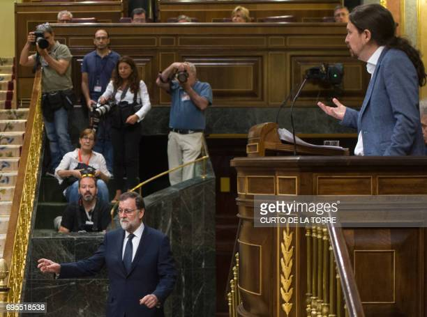 Spanish Prime Minister Mariano Rajoy walks as Unidos Podemos Party's leader Pablo Iglesias speaks at the Congress of Deputies in Madrid on June 13...
