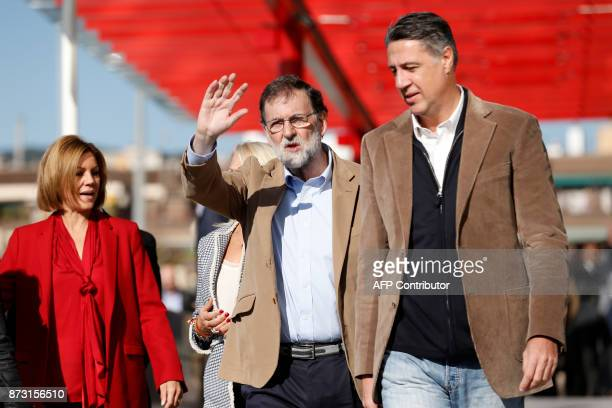Spanish Prime Minister Mariano Rajoy waves next to Spanish Minister of Defence Maria Dolores de Cospedal and leader of the Catalan Popular Party...