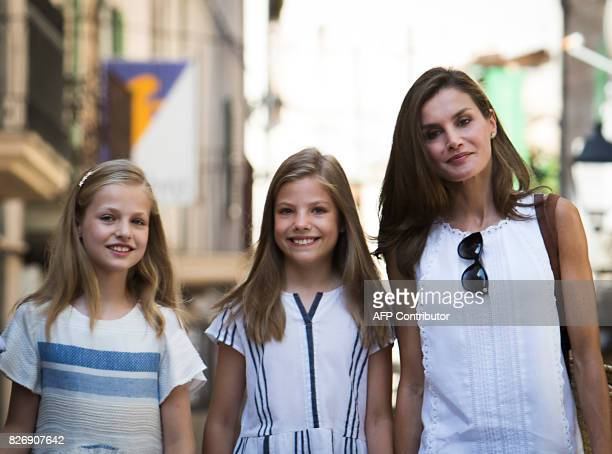 Spanish Queen Letizia and her daughters Spanish crown princess Leonor and Spanish crown princess Sofia pose as they walk down a street in the village...