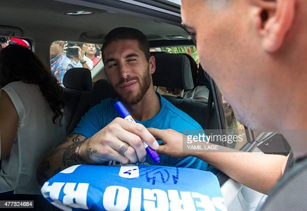 Spanish Real Madrid football team player Sergio Ramos winks as he autographs a jersey in Havana on June 16 2015 Ramos is in Cuba as UNICEF ambassador...