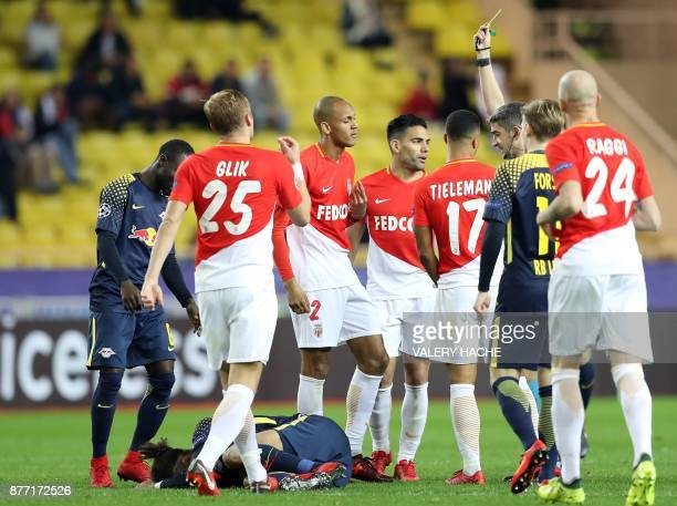 Spanish referee Alberto Undiano Mallenco gives a yellow card to Monaco's Brazilian midfielder Fabinho during the UEFA Champions League group G...