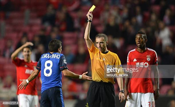 Spanish referee Davd Fernandez Borbalan shows yellow card to AS Monaco's Portuguese defender Joao Moutinho during the UEFA Champions League group C...