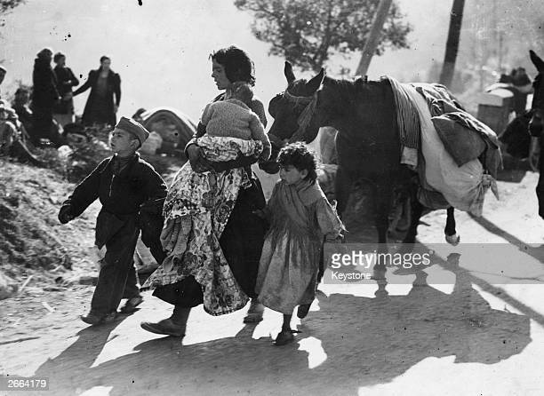 Spanish refugees on the road during the Spanish Civil War followed by a donkey