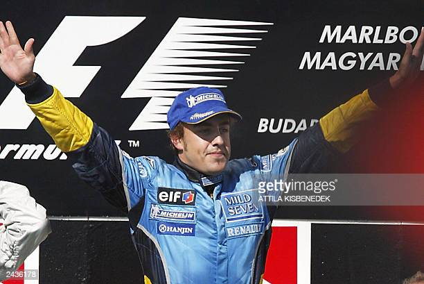 Spanish Renault driver Fernando Alonso jubilates on the podium of the Hungaroring racetrack near Budapest 24 August 2003 after the Hungarian Formula...