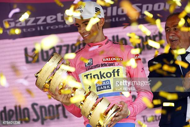 Spanish rider Alberto Contador holds up his trophy as he celebrates on the podium after winning the 98th Giro d'Italia Tour of Italy in Milan on May...