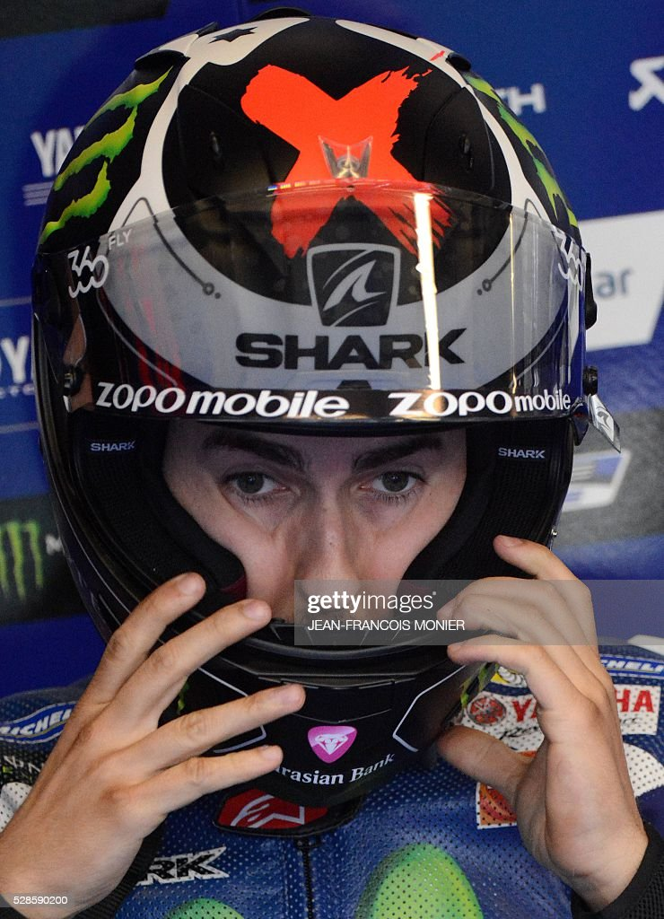 Spanish rider Jorge Lorenzo dons his helmet in the pit before a motoGP free practice session, ahead of the French motorcycling Grand Prix, on May 6, 2016 in Le Mans, northwestern France. / AFP / JEAN