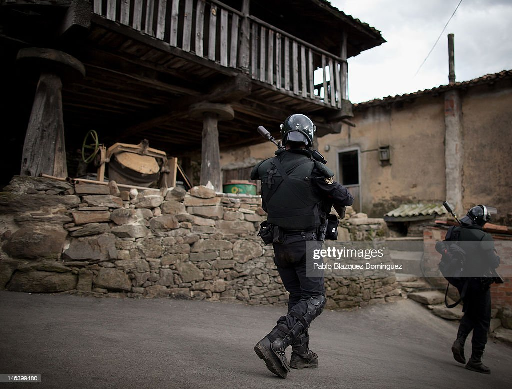 Spanish riot police walk next to a traditional Asturia's wheat storage, Orreo, in Figaredo near Mieres after searching for miners on June 15, 2012 in northern Spain. Spanish coal miners are staging a nationwide strike organised by unions opposed to subsidy reductions from 300 million to 110 million Euros.