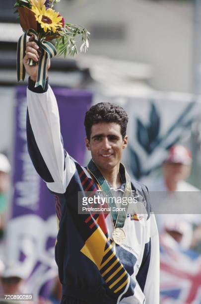Spanish road racing cyclist Miguel Indurain of the Spain team pictured raising one arm in the air on the medal podium after finishing in first place...