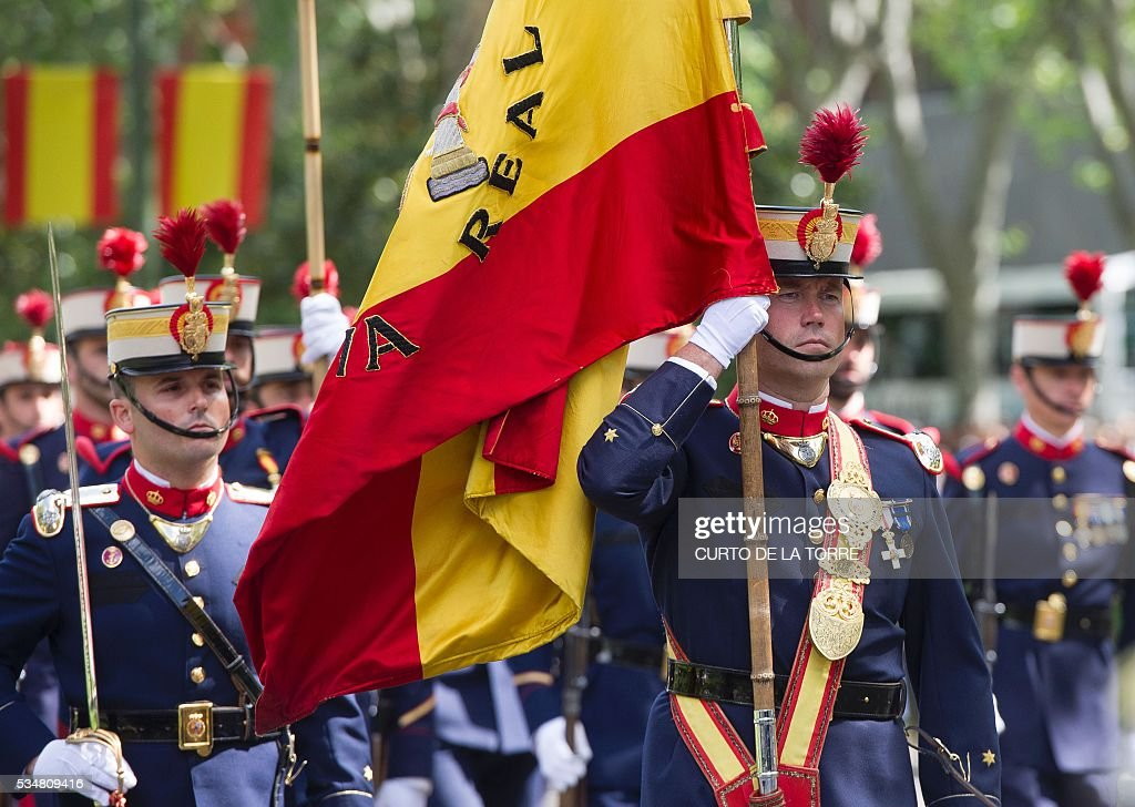 Spanish Royal guards hold the Spanish flag as the march during the 2016 Armed Forces Day parade in Madrid on may 27, 2016. / AFP / CURTO