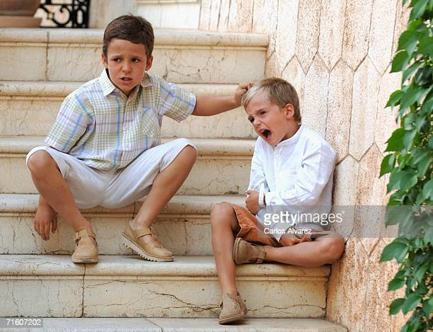 Spanish Royals Froilan and Pablo Nicolas Urdangarin sit on the steps during a photocall at Marivent Palace on August 6 2006 in Mallorca Spain