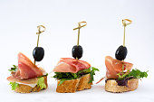 Spanish serrano ham skewer with olive and lettuce isolated on white background