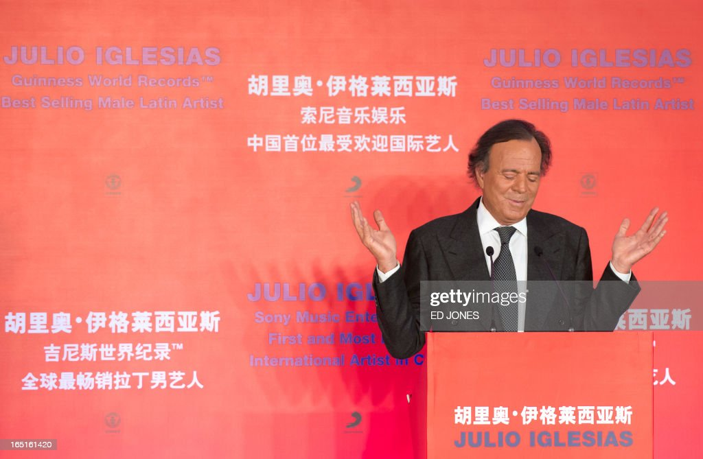 Spanish singer-songwriter Julio Iglesias gestures after being presented with a Guinness World Record for 'Best Selling Latin Artist in the World' at a press conference in Beijing on April 1, 2013. Iglesias was promoting his upcoming tour of China, and recieving a Guinness World Record for 'Best Selling Latin Artist in the World' after selling 250 million albums. AFP PHOTO / Ed Jones