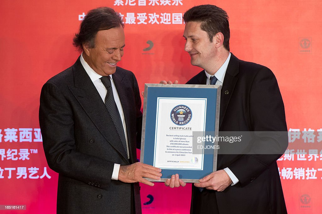 Spanish singer-songwriter Julio Iglesias (L) is presented with a Guinness World Record for 'Best Selling Latin Artist in the World' at a press conference in Beijing on April 1, 2013. Iglesias was promoting his upcoming tour of China, and recieving a Guinness World Record for 'Best Selling Latin Artist in the World' after selling 250 million albums. AFP PHOTO / Ed Jones