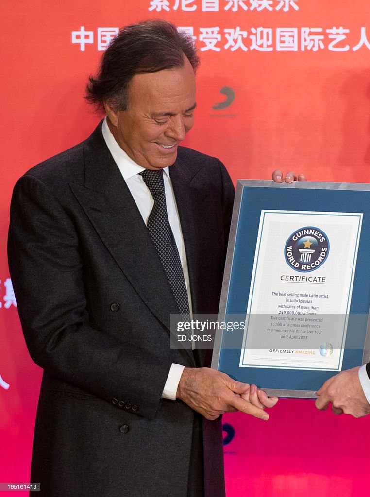 Spanish singer-songwriter Julio Iglesias is presented with a Guinness World Record for 'Best Selling Latin Artist in the World' at a press conference in Beijing on April 1, 2013. Iglesias was promoting his upcoming tour of China, and recieving a Guinness World Record for 'Best Selling Latin Artist in the World' after selling 250 million albums. AFP PHOTO / Ed Jones