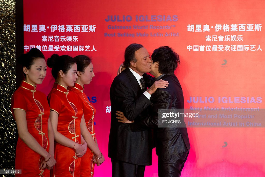 Spanish singer-songwriter Julio Iglesias (C) kisses Chinese pianist Lang Lang (R) at a press conference in Beijing on April 1, 2013. Iglesias was promoting his upcoming tour of China, and recieving a Guinness World Record for 'Best Selling Latin Artist in the World' after selling 250 million albums. AFP PHOTO / Ed Jones