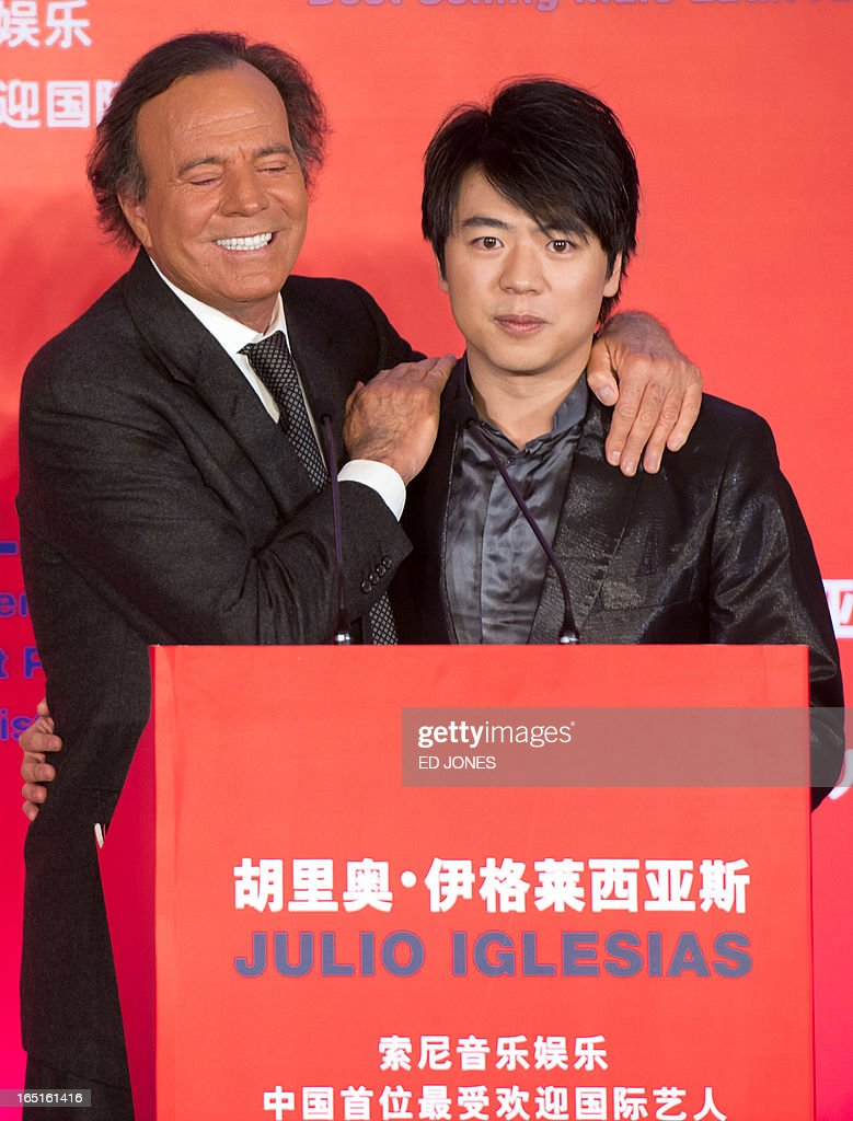 Spanish singer-songwriter Julio Iglesias (L) poses with Chinese pianist Lang Lang at a press conference in Beijing on April 1, 2013. Iglesias was promoting his upcoming tour of China, and recieving a Guinness World Record for 'Best Selling Latin Artist in the World' after selling 250 million albums. AFP PHOTO / Ed Jones